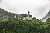 Blick auf Schloss Neuschwanstein mit Wolken und Bergen im Hintergrund, Schwangau, Oberbayern, Deutschland