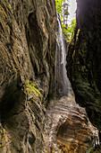 Waterfall between the rock faces of the Partnachklamm, Garmisch-Partenkirchen, Upper Bavaria, Germany