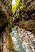 View through the rock walls and the river of the Partnachklamm, Garmisch-Partenkirchen, Upper Bavaria, Germany
