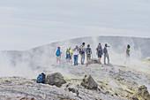 Hikers walking through fumaroles smoke on Gran Cratere rim, Vulcano Island, Aeolian Islands,  Sicily, Italy,
