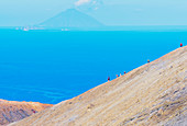 Hikers walking on Gran Crater rim, Vulcano Island, Aeolian Islands, Sicily, Italy