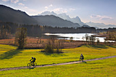 Cyclists, view over the Geroldsee to the Zugspitze massif with Alpspitze, Zugspitze and Waxenstein, Werdenfelser Land, Bavaria, Germany