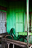A green bicycle leans against a house painted green in Palangkaraya, Central Kalimantan, Borneo Indonesia.