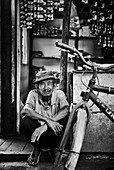 An Indonesian elder sits in the doorway of his shop at a market in Palangkaraya, Central Kalimantan, Borneo Indonesia