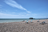 Brighton Beach with people and deck chairs on a spring day, Brighton, East Sussex, UK.