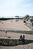 A view of Brighton Beach looking towards the burnt remains of West Pier, Brighton, East Sussex, UK.