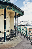 Tables and chairs at the seaside on Brighton Beach, looking through to the Brighton Palace Pier, East Sussex, UK.