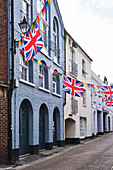 A street view of Courthouse Street buildings decorated wtih bunting for the Jack In the Green festival, in Old Town, Hastings, East Sussex, UK.
