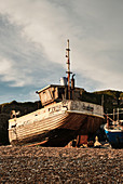 A traditional wooden fishing boat sits on the pebbled sea shore of Rock A Nore beach at sunset, Hastings, East Sussex, UK.