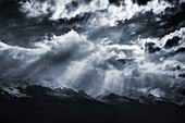 Rays of sunlight filter through dramatic clouds onto a snow topped mountain range outside of Queenstown, South Island, New Zealand.