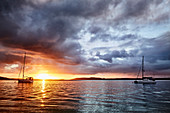 Sunset golden hour at Nelson Bay, New South Wales Australia while a storm rolls over with boats moored on the water.