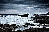 Waves breaking on rocks on a dark stormy day in autumn at Tomaree National Park, Nelson Bay, New South Wales, Australia