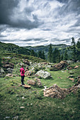 Woman stands on a rock and takes cell phone pictures of the red rocks at the red castle, Nockberge Biosphere Park, Carinthia, Austria, Europe.