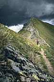 Woman with dog backpack on the Klomnockweg heading north, between Mallnock and Klomnock with a view of the Klomnock, Nockberge Biosphere Park, Carinthia, Austria, Europe.