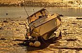Motorboat in Brittany in the golden evening light at low tide, Brittany, France, Europe