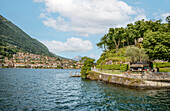 Ship landing stage on the promenade of Isola Comacina on Lake Como seen from the lake side, with the town of Ossuccio in the background, Lombardy, Italy