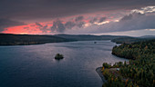Camping in a VW bus on the lonely shore of a lake on Wilderness Road in Northern Sweden, in the sunset from above