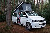 Frau bei Vanlife Camping mit VW Bus im Wald in Schweden, Siljansee
