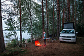 Woman in outdoor clothing at Vanlife Camping with a VW bus in the forest in Sweden, at the lake with a campfire, Lake Siljan