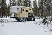 Van im Tiefschnee im winterlichen Wald in Lappland, Arvidsjaur, Schweden