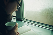 Young woman reads in the VW bus, VW T6 California, Bulli