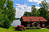 Typical red Swedish house overlooking a lake, Gräfsnäs, Västra Götaland, Sweden