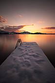 View of the sunset at the Hopfensee, in the foreground a snow-covered footbridge Bavaria, Germany, Europe