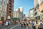 Pedestrians on a car-free Sunday on Ginza shopping street, Tokyo, Japan