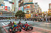 Shibuya street scene with a group of tourists in go-karts, Tokyo, Japan
