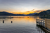 Sunset over Lake Millstatt. Bathing fun on the beach. In the background you can see the alpine mountain landscape, Carinthia; Austria, Europe
