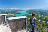 A woman looks from the Pyramidenkogel observation tower to Lake Wörthersee, Carinthia, Austria