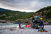Albania, Southern Europe, young couple in front of off-road vehicle with roof tent, campfire, river, Vjosa, Permet