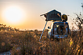 Albania, Southern Europe, young man looks out of the roof tent on an off-road vehicle in the evening sun