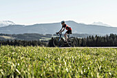 Racing cyclists on the Bichlpass; in the background the Teisenberg, Neukirchen, Bavaria, Germany