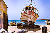 A boat is jacked up on simple beams right by the sea on the island of Cape Verde, the island of Boa Vista