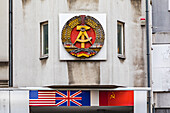 The symbols of the GDR and the occupying powers are still displayed at Checkpoint Charlie in Berlin today