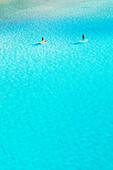 People paddleboarding at Cala Mitjana, Minorca, Balearic Islands. Spain