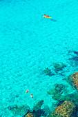 Kanufahren und Schwimmen in Cala Mitjana, Menorca, Balearen. Spanien