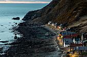Dusk at Crovie, seaside village, Moray Firth, lighting the quay, Aberdeenshire, Scotland, UK