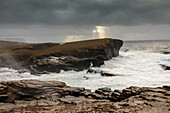 Storm, surf breaker, Yesnaby cliff, sunbeam through clouds, cliffs, Orkney, Scotland UK
