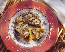 Small chocolate tart with almonds and orange sauce