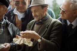 Men examining truffles at the truffle market in Alba