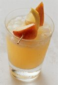 Nectarine drink with ice cubes in glass