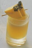 Papaya drink in glass with papaya pieces on cocktail stick
