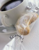 Wrapped almond crescents and a cup of coffee