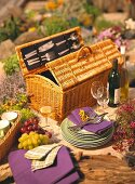 Still life with picnic basket, crockery, glasses and wine