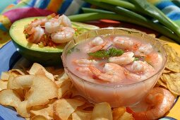 Shrimps in a glass bowl and avocado stuffed with shrimps
