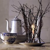 Candle in glass with twigs as winter table decoration