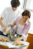 Young couple baking, with mixing bowl, hand blender & cookbook