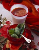Tomato soup in glass and basil dumplings in bowl